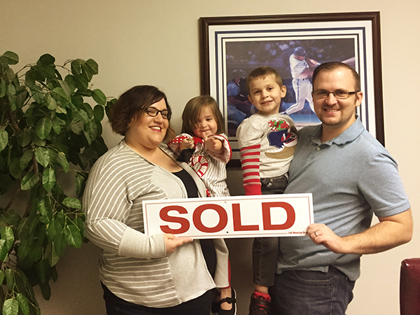 Family picture with SOLD sign after closing